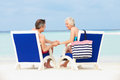 Senior couple on beach relaxing in chairs smiling Stock Photography