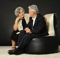 Senior couple on black background spending time together sitting cushions Royalty Free Stock Photography