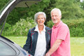 Senior couple with black car standing at a Stock Images