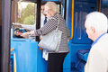 Senior couple boarding bus and using pass looking at each other smiling Royalty Free Stock Image