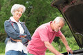 Senior couple at broken car standing together a Stock Image