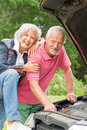Senior couple at broken car standing together a Stock Images