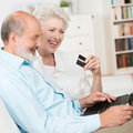 Senior couple buying online sitting together on a sofa with their laptop computer and bank card laughing as they make their choice Stock Photography