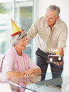 Senior  couple celebrating  with a birthday cake Royalty Free Stock Images