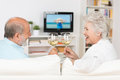 Senior couple celebrating with white wine clinking their glasses and toasting each other a laugh as they sit on a sofa in Royalty Free Stock Photography