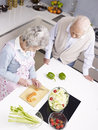 Senior couple chatting in kitchen high angle view of a talking while preparing meal Royalty Free Stock Image