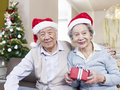 Senior couple with christmas hats portrait of an asian and gifts Royalty Free Stock Image