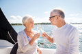 Senior couple clinking glasses on boat or yacht sailing age travel holidays and people concept happy champagne sail deck floating Royalty Free Stock Photos
