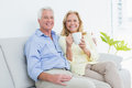 Senior couple with coffee cup sitting on sofa relaxed in a bright house Royalty Free Stock Photo