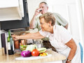Senior couple cooking together seniors in kitchen at home while drinking wine Stock Image