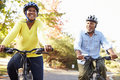 Senior couple on cycle ride in countryside smiling Stock Images