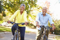 Senior couple on cycle ride in countryside smiling Royalty Free Stock Images