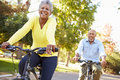 Senior couple on cycle ride in countryside smiling Royalty Free Stock Photo