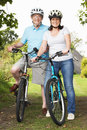 Senior couple on cycle ride in countryside smiling to camera Royalty Free Stock Photo