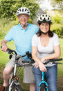 Senior couple on cycle ride in countryside smiling to camera Royalty Free Stock Photography