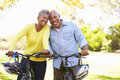 Senior couple on cycle ride in countryside smiling to camera Royalty Free Stock Photos