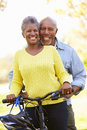 Senior couple on cycle ride in countryside smiling to camera Stock Photo