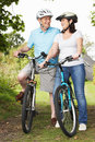 Senior couple on cycle ride in countryside smiling to each other Royalty Free Stock Image