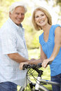Senior Couple On Cycle Ride In Park Stock Photography