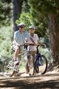 Senior couple, in cycling helmets, mountain biking on woodland trail, smiling, portrait Royalty Free Stock Photo
