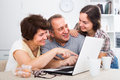 Senior couple and daughter with laptop at home