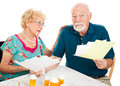 Senior couple distressed by medical bills going over their they are confused and overwhelmed white background Royalty Free Stock Photo