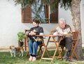 Senior couple with dogs enjoying in courtyard sitting drinking coffee reading a book and playing Stock Images