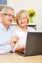 Senior couple doing online shopping with laptop computer and credit card Stock Image