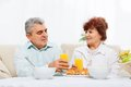 Senior couple drink orange juice breakfast having sitting at table sofa home living room or kitchen Royalty Free Stock Images