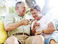 Senior couple drinking wine outside on patio photo of a Royalty Free Stock Image