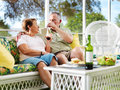 Senior couple drinking wine outside on patio relaxing iwne Stock Photos