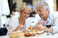 Senior couple eating appetizers outdoors Royalty Free Stock Photo