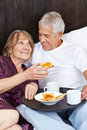 Senior couple eating breakfast in bed happy a hotel Royalty Free Stock Images