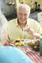 Senior Couple Eating Meal Together In Kitchen Royalty Free Stock Photo