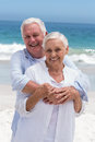 Senior couple embracing with arms around at the beach Royalty Free Stock Photography