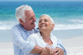Senior couple embracing with arms around at the beach Royalty Free Stock Images