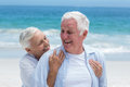 Senior couple embracing with arms around at the beach Stock Image