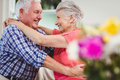 Senior couple embracing each other in living room Stock Image