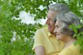 Senior couple embracing outdoors portrait of beautiful on the walk against green leaves background Stock Photography