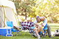Senior couple enjoying camping holiday in countryside Stock Photos