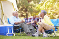 Senior couple enjoying camping holiday in countryside Royalty Free Stock Photography