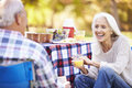 Senior couple enjoying camping holiday in countryside smiling Stock Photography