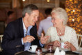 Senior couple enjoying cup of coffee in restaurant smiling to each other Royalty Free Stock Photo