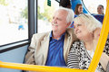 Senior couple enjoying journey on bus with arm around wife looking away from camera smiling Stock Image