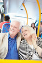 Senior couple enjoying journey on bus looking out the window smiling Stock Image