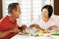 Senior Couple Enjoying Meal At Home Stock Photos