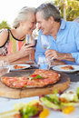 Senior couple enjoying meal in outdoor restaurant smiling Royalty Free Stock Photography