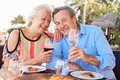 Senior couple enjoying meal in outdoor restaurant smiling Royalty Free Stock Photos