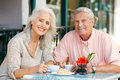 Senior Couple Enjoying Snack At Outdoor Cafe Stock Photography