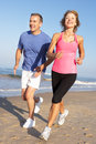 Senior Couple Exercising On Beach Royalty Free Stock Photo
